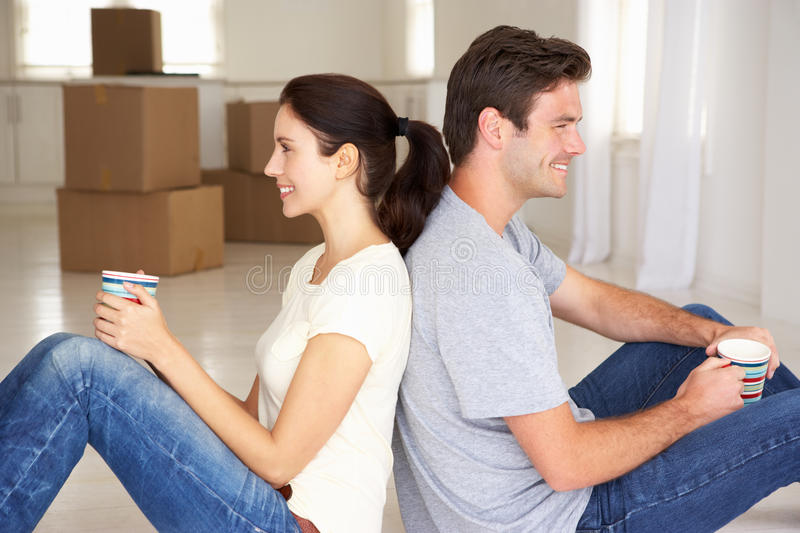 Couple in new home drinking tea. Happy couple in new home drinking tea sitting back to back smiling off camera stock image