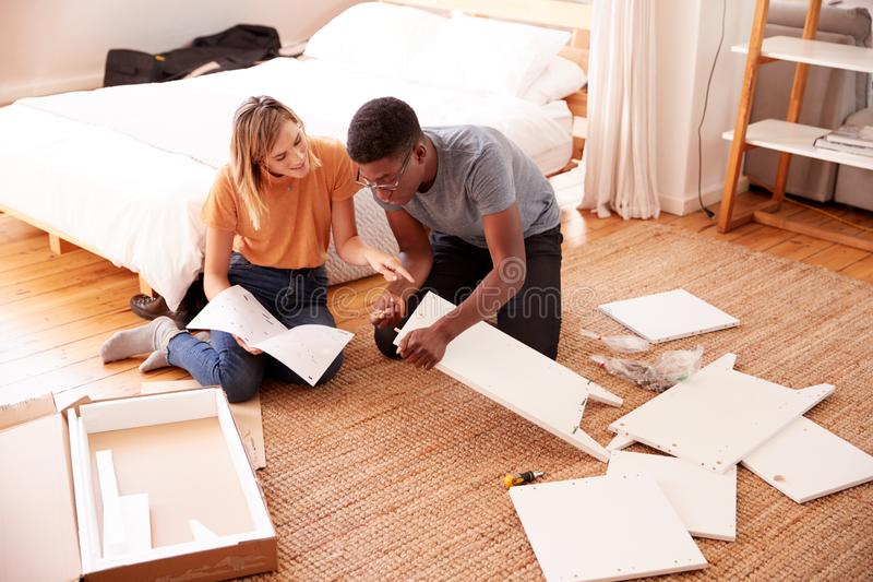 Couple In New Home Putting Together Self Assembly Furniture stock photography