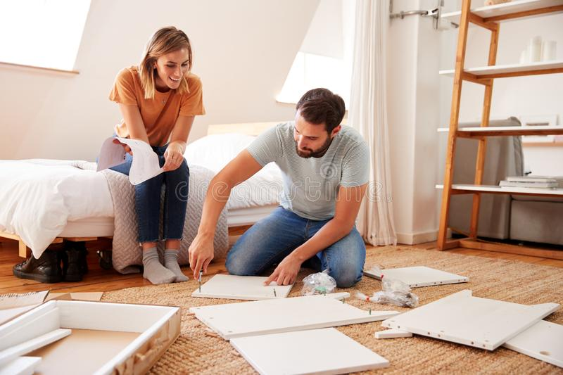 Couple In New Home Putting Together Self Assembly Furniture stock images