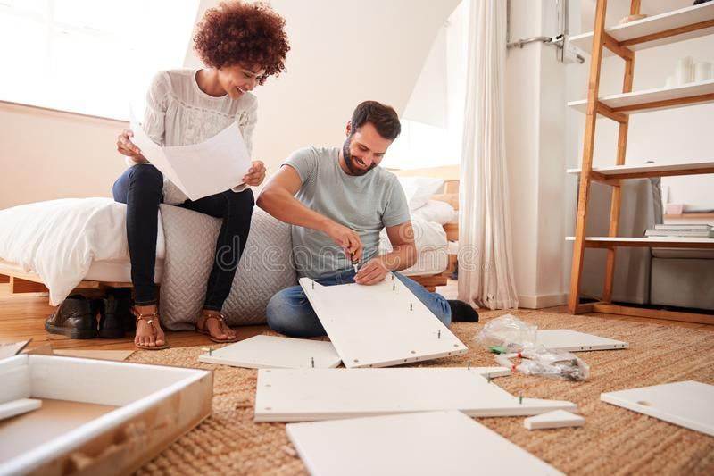 Couple In New Home Putting Together Self Assembly Furniture stock photo