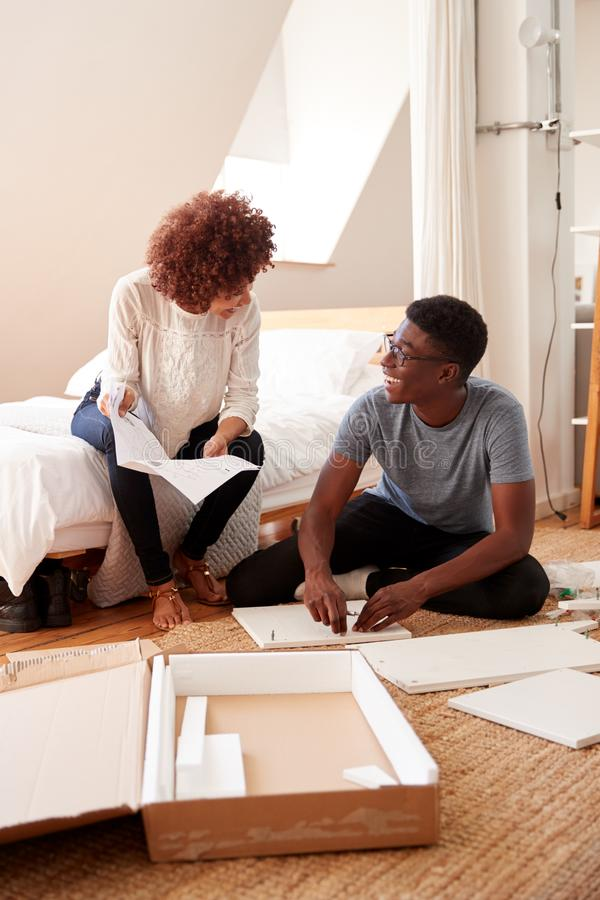 Couple In New Home Putting Together Self Assembly Furniture royalty free stock photography