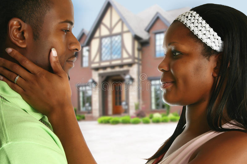 Couple with New House. Attractive young african american couple in front of new home stock photography