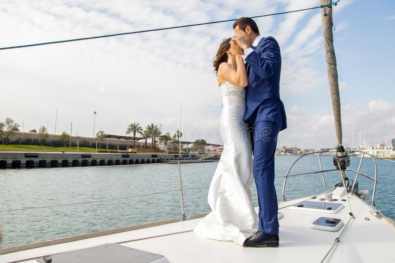 Couple of newly married lovers dance on the deck of a sailboat stock photography