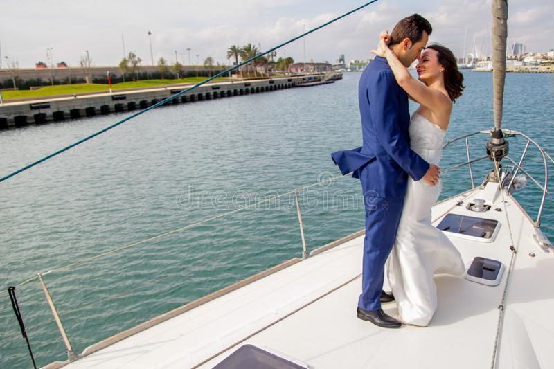 Couple of newly married lovers pose on the bow of a sailboat during their honeymoon. stock photography