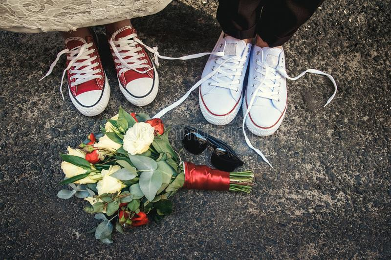 Couple of newly weddings with funny equal sneakers and wedding bouquet, sunglasses. Wedding details royalty free stock photography