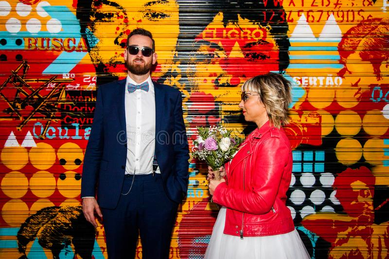 Couple of newlyweds pose in front of a graffiti metal blind stock images