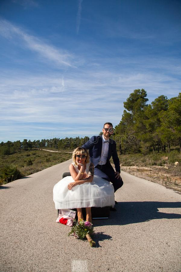 Couple of newlyweds pose with a sofa in the middle of a lonely road royalty free stock photography