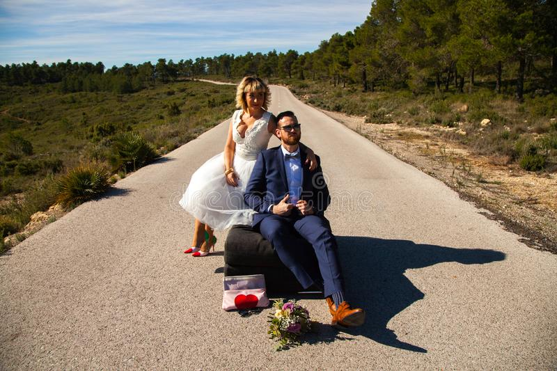 Couple of newlyweds pose with a sofa in the middle of a lonely road stock photo