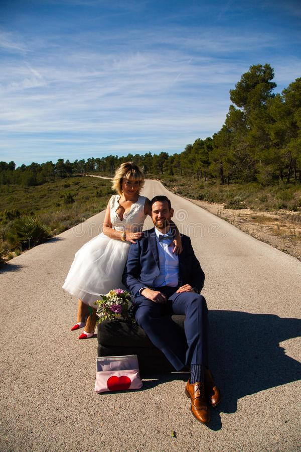 Couple of newlyweds pose with a sofa in the middle of a lonely road stock images