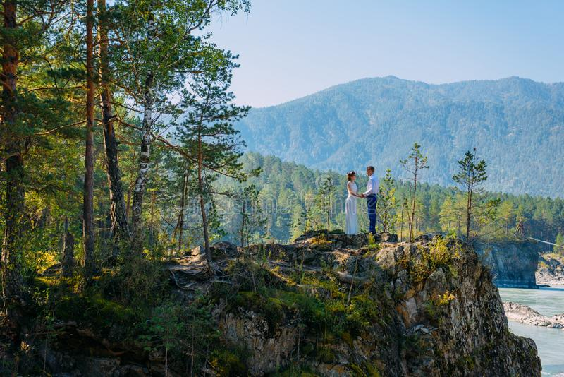 A couple of newlyweds stand in the wild nature and gaze at each other. In the background, forest, river and mountains stock photos