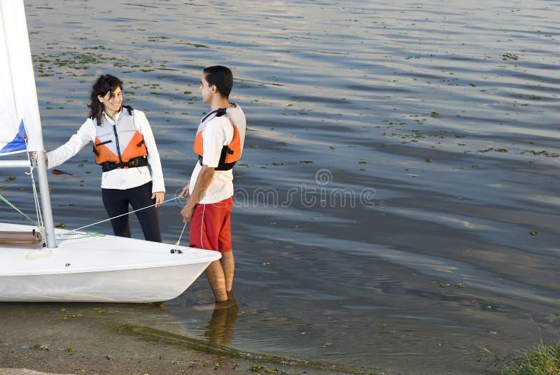 Couple Next to Sailboat on Water - Horizontal
