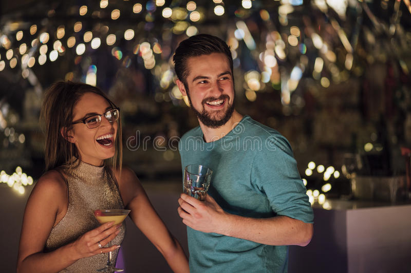 Couple In A Nightclub. Young adult couple are socialising in a nightclub with cocktails. Theya re laughing and looking at someone out of the frame royalty free stock photo