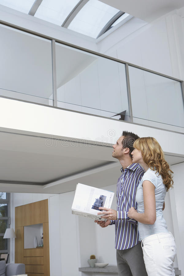 Couple Observing New Home. Low angle view of a young couple observing new home royalty free stock photos