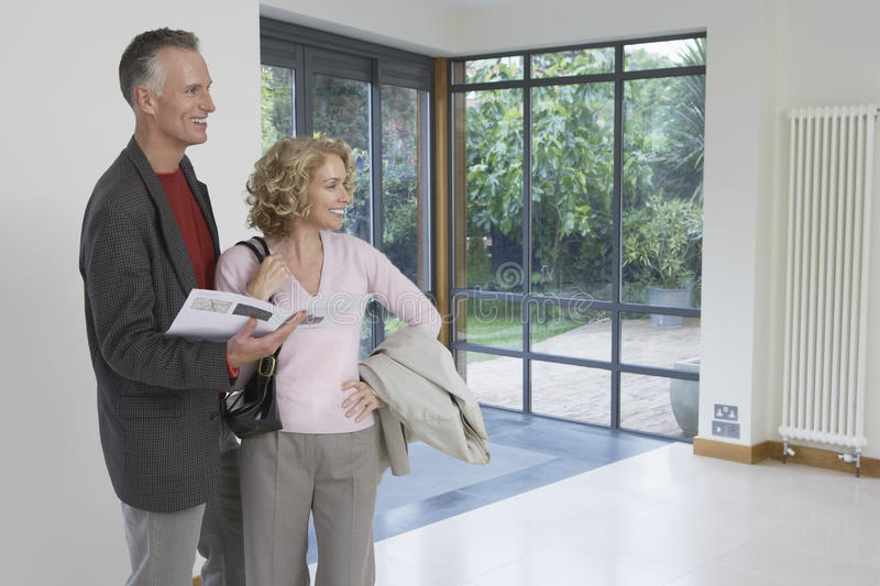 Couple Observing New Property. Happy couple with brochure observing new property stock image