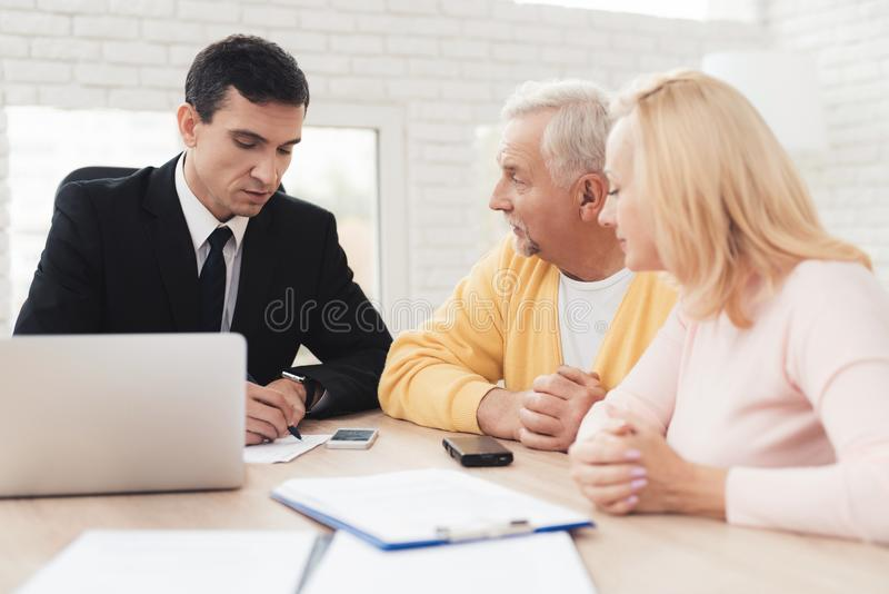 A couple of old people came to a consultation with a lawyer. The lawyer communicates with a man and a woman. stock image