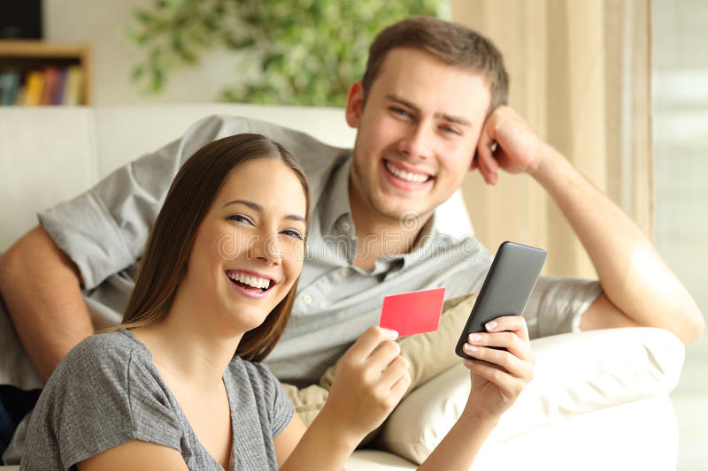 Couple of online buyers posing. Couple of online buyers buying with credit card and smart phone posing and looking at camera stock photos