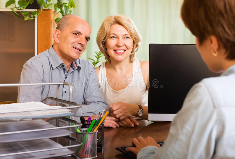 Couple opening account in bank. Positive senior couple opening saving account in bank stock images