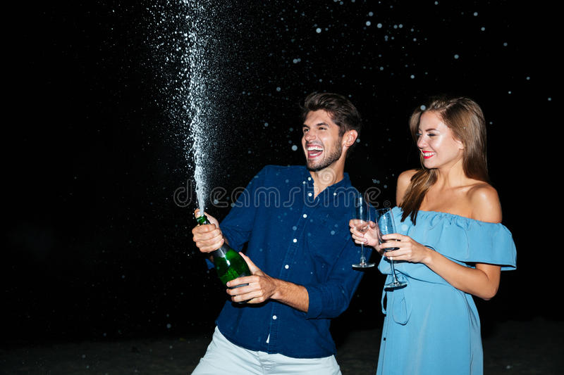 Couple opening bottle of champagne and having fun at night stock images