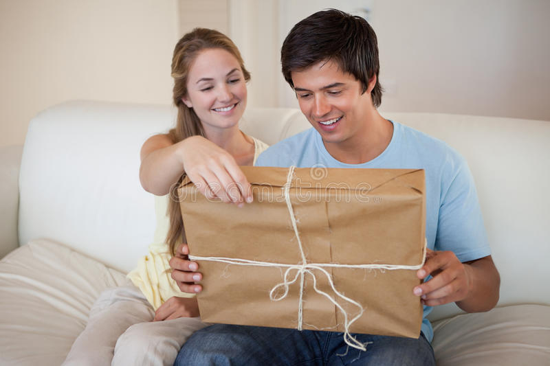 Couple opening a package. In their living room royalty free stock image