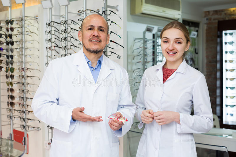 Couple ophthalmologists working in optics store. Couple of friendly ophthalmologists working in modern optics store royalty free stock photography