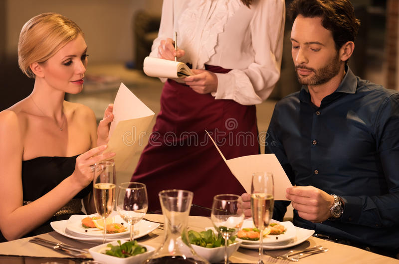 Couple ordering food. Cheerful couple with menu in a restaurant making order. Young waitress offering to young couple tasty dishes. Young couple ordering for stock photo