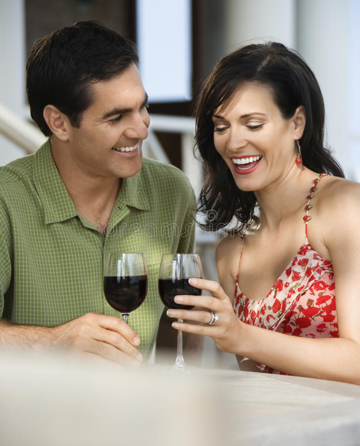 Couple at Outdoor Cafe. Couple drinking red wine at an outdoor cafe. Vertical shot royalty free stock photo