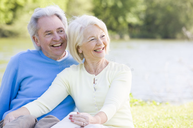 Couple outdoors at park by lake smiling stock photography