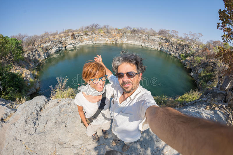 Couple with outstretched arms taking selfie at Otjikoto Lake, one of the only two permanent natural lake in Namibia, Africa. stock photos