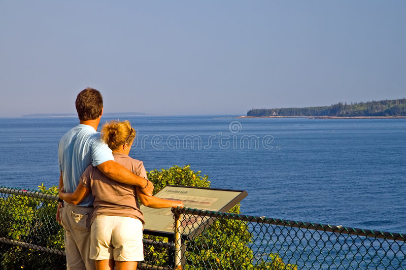 Couple overlooking ocean. A view of a young couple on vacation, sightseeing at the Bass Harbor Lighthouse, Maine, stopping to take in the scenery along the royalty free stock image