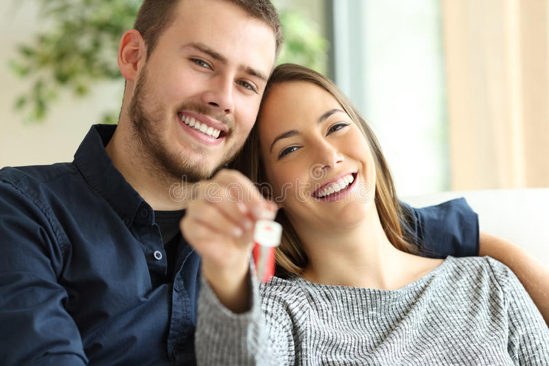 Couple of owners showing house keys royalty free stock photos