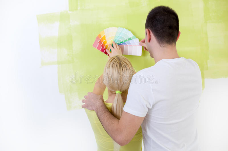 Couple with paint swatches. Choosing colors for painting new home stock images