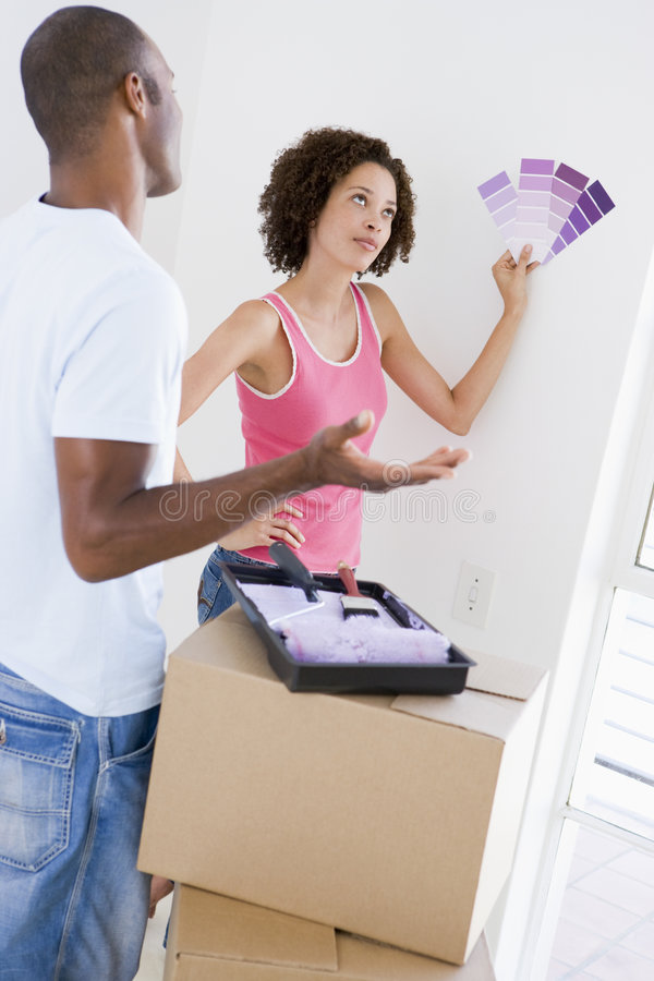 Couple with paint swatches in new home undecided. What shade of colour royalty free stock photography