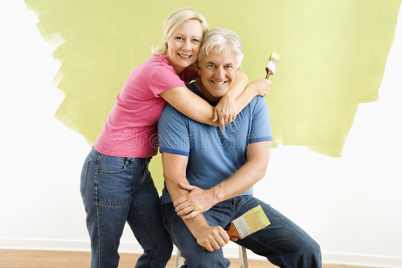 Couple with paintbrushes. Portrait of smiling adult couple sitting in front of half-painted wall with paintbrushes royalty free stock image