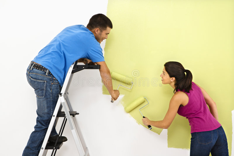 Couple painting home. Attractive young adult couple painting interior wall of house royalty free stock photos
