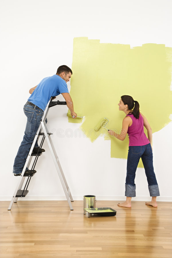Couple painting house. Attractive young adult couple painting interior wall of house royalty free stock photography
