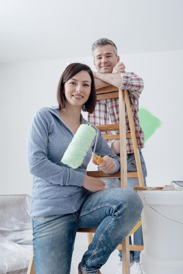 Couple painting their house. Happy couple renovating their house and painting a room, they are leaning on a ladder and posing with paint rollers stock images
