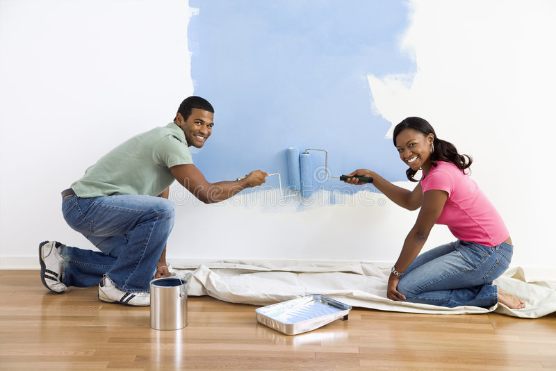 Couple painting wall blue. stock image