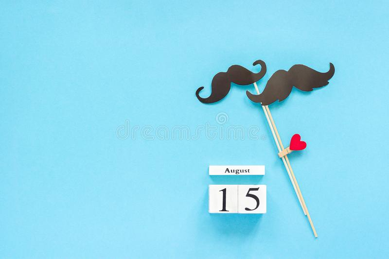 Couple paper mustache props fastened clothespin heart and calendar 15 August on blue background. Concept Homosexuality gay love. International Gay Day Top view stock images
