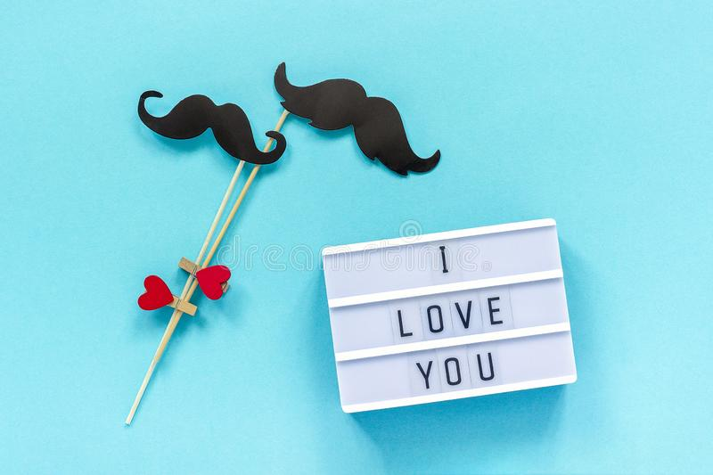 Couple paper mustache props and light box with text I love you on blue background. Concept Homosexuality gay love. National Day. Couple paper mustache props and stock photo