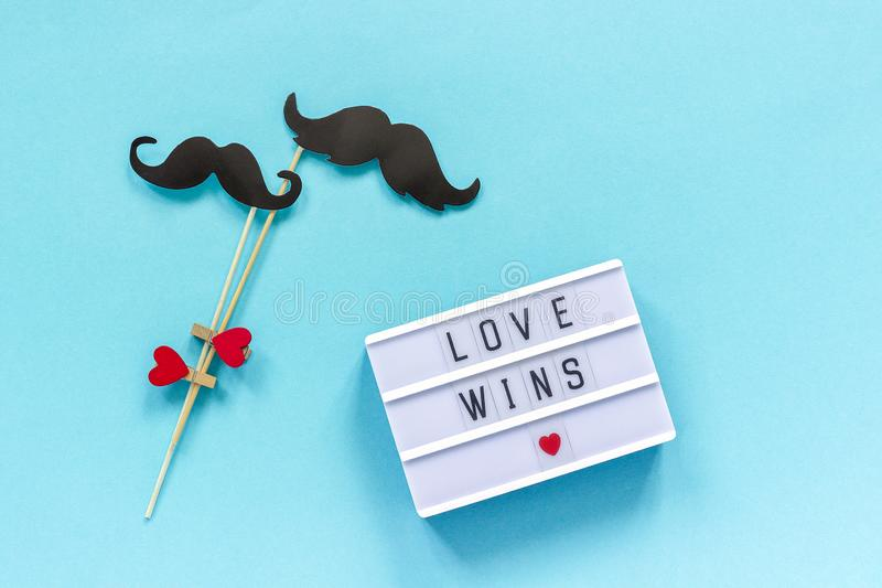 Couple paper mustache props and light box with text Love wins on blue background. Concept Homosexuality gay love. National Day. Couple paper mustache props and royalty free stock image