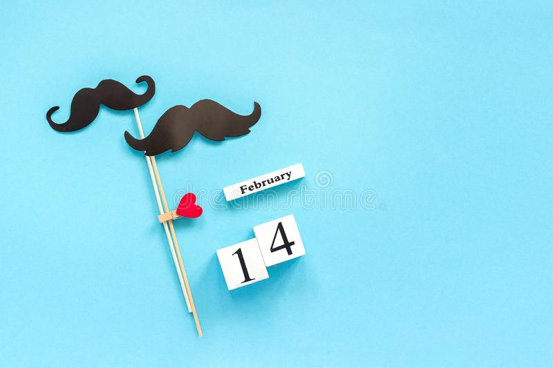 Couple paper mustache props fastened clothespin heart and calendar February 14 on blue background. Concept Homosexuality gay love. Couple paper mustache props on royalty free stock photos