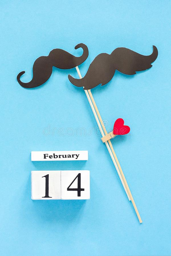 Couple paper mustache props fastened clothespin heart and calendar February 14 on blue background. Concept Homosexuality gay love. Couple paper mustache props on royalty free stock images