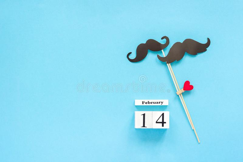 Couple paper mustache props fastened clothespin heart and calendar February 14 on blue background. Concept Homosexuality gay love. Couple paper mustache props on stock images