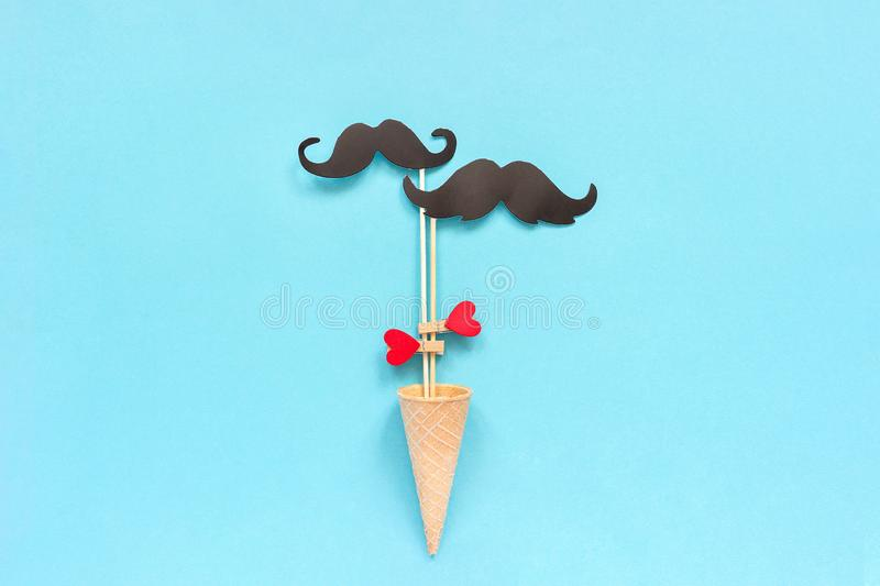 Couple paper mustache props on stick fastened clothespin heart in ice cream waffle cone on blue background. Concept Homosexuality. Gay love. International Gay stock photography