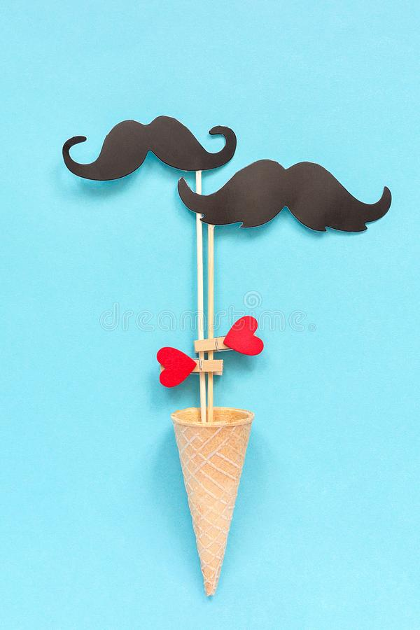 Couple paper mustache props on stick fastened clothespin heart in ice cream waffle cone on blue background. Concept Homosexuality. Gay love. International Gay royalty free stock photo