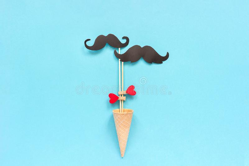 Couple paper mustache props on stick fastened clothespin heart in ice cream waffle cone on blue background. Concept Homosexuality. Gay love. International Gay stock images