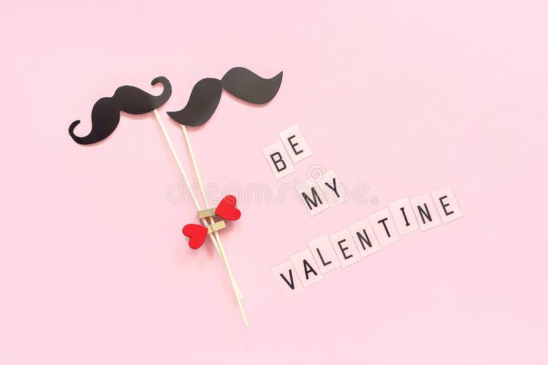 Couple paper mustache props on stick fastened clothespin heart and text Be my Valentine on pink background Concept Homosexuality. Gay love. Valentine`s Day royalty free stock image