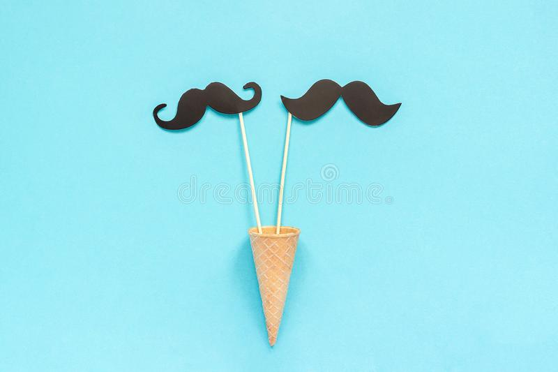 Couple paper mustache props on stick in ice cream waffle cone on blue background. Concept Homosexuality gay love. International. Gay Day or Valentine`s Day stock photography