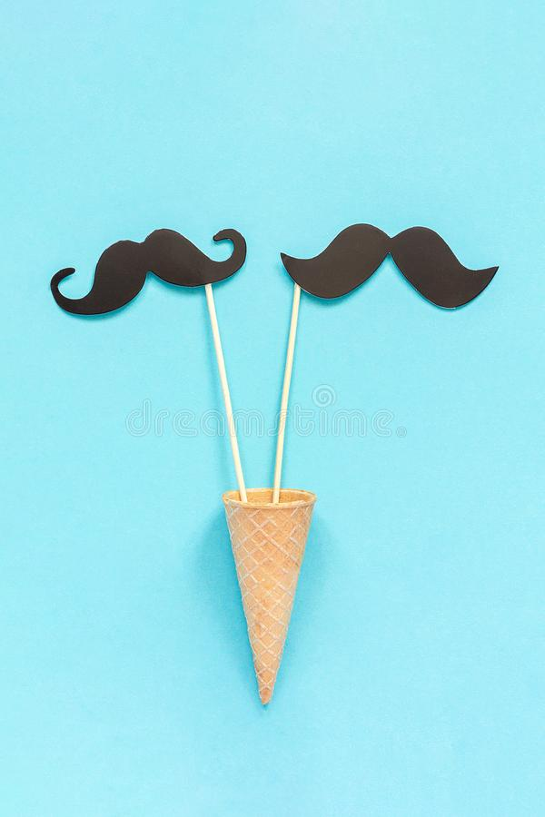 Couple paper mustache props on stick in ice cream waffle cone on blue background. Concept Homosexuality gay love. International. Gay Day or Valentine`s Day royalty free stock photos