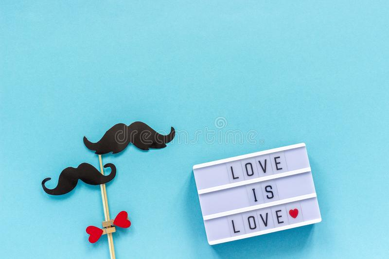 Couple paper mustache props on stick and light box with text Love is love on blue background. Concept Homosexuality gay love. Couple paper mustache props on royalty free stock photos